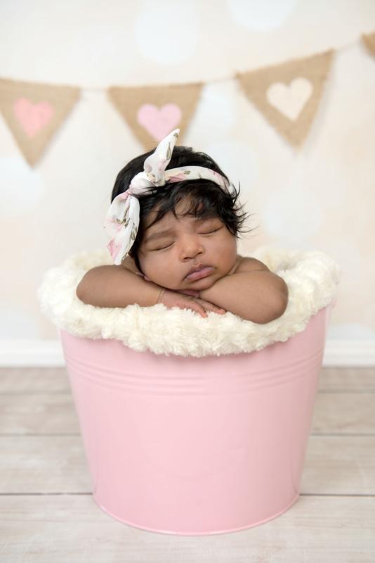 cute newborn baby girl in pink bucket